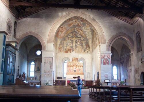 08 - L'interno con i tre archi a sesto acuto sorretti da pilastri che dividono la navata dalle absidi; sulla lunetta dell'abside centrale la Crocifissione